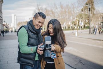 Cheerful Chinese Couple around Palacio Real of Madrid with a big camera