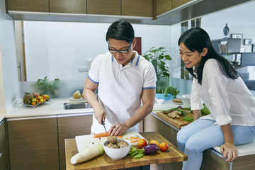 Husband and wife preparing food in the kithen