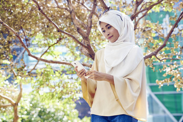 Beautiful Malay woman in a Hijab at the park using her mobile