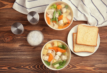 Composition with delicious turkey soup in two bowls on wooden table