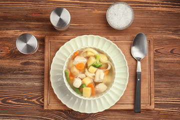 Bowl with delicious turkey soup on wooden table