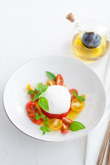 Delicious caprese salad with ripe cherry tomatoes and mozzarella cheese with fresh basil leaves and olive oil. Italian healthy food concept with copy space