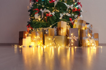 Gift boxes under beautiful fir tree decorated for Christmas