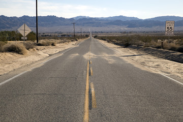 Empty asphalt road through a desert in California, USA