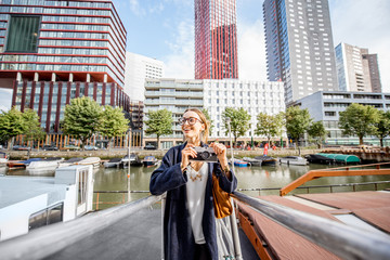 Spoed Fotobehang Rotterdam Young woman traveling at the modern harbor with skyscrapers on the background in Rotterdam city