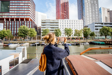 Fototapete - Young woman photographing modern skyscrapers standing on the harbor in Rotterdam city