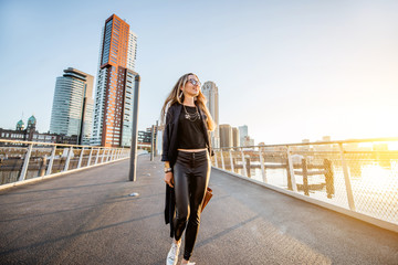 Fototapete - Lifestyle portrait of a young stylish businesswoman walking the bridge during the morning in Rotterdam