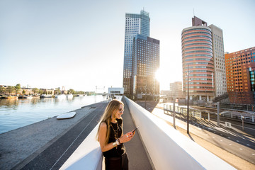 Fototapete - Lifestyle portrait of a stylish woman standing with phone on the modern bridge with skyscrapers on the background during the morning in Amsterdam city