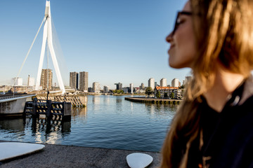 Fototapete - Young woman tourist enjoying beautiful morning cityscape view in Rotterdam city. Woman is out of focus