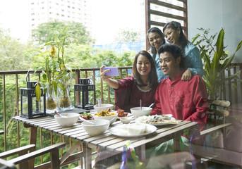 Happy family taking selfies at the balcony during Hari Raya