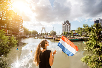 Spoed Fotobehang Rotterdam Young woman tourist standing back with dutch flag at the old harbor in Rotterdam city
