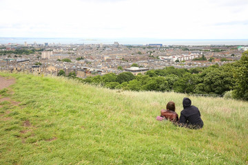 Couple enjoying the view overlooking beautiful Edinburg, Scotland.