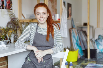 Picture of talented young crafts woman with pretty face and cute smile wearing apron dirty with paints having rest after she finished work, sitting on chair in modern creative workshop interior
