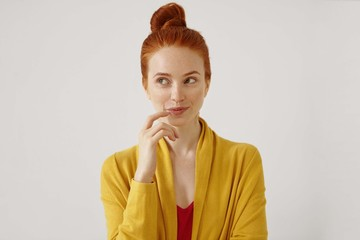 Portrait of stunning young female wearing her ginger hair in knot touching lips, looking away with sly cunning and cunning smile. Pretty girl having thoughtful dreamy look posing at studio wall