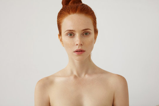 Horizontal portrait of naked beautiful female with freckled healthy skin and ginger hair tied in knot, looking with her green eyes and slightly opened mouth into camera, having mysterious look