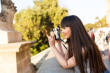 Eurasian woman with a vintage polaroid camera in Barcelona