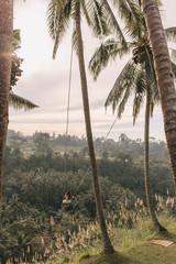 Woman on a swing against a beautiful landscape in Bali