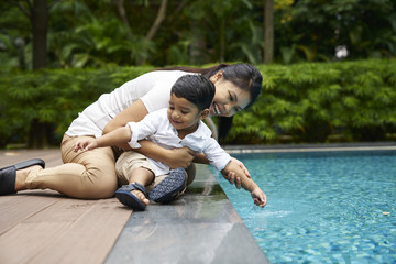Smiling Mother and son bonding by the poolside
