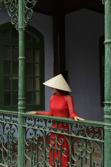 Woman wearing traditional clothing standing on balcony, Hoi An, Vietnam