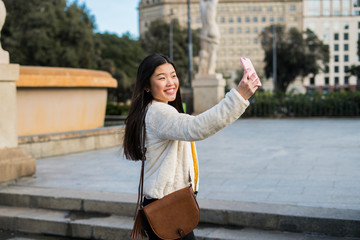 Chinese young girl taking a selfie with her pink smartphone and smiling in plaza catalunya, barcelona, spain