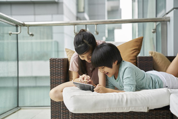 Siblings sharing an electronic tablet