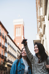 Chinese and european young and pretty women doing sight-seeing and pointing somewhere in the streets of Madrid