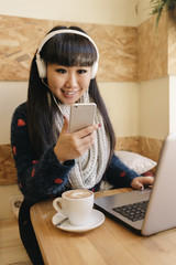 Businesswoman listening to music in a cafe