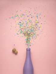 Splashing hard / Creative concept photo of champagne bottle with confetti on pink background.