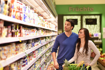 young couple shopping at the supermarket // junges Paar beim Einkauf am Regal im Supermarkt