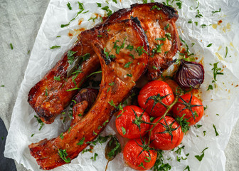 Pork middle chop roast with sweet and sour souce, baked tomatoes and red onion