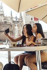 Chinese women sitting at table making selfie