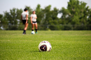 Women Playing Soccer Kicking Soccer Ball on Green Grass Turf