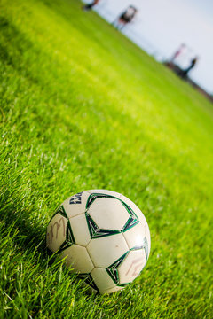 Soccer Ball on a Green Field with the Theory of Thirds and Depth of Field with People in the Background Playing Soccer