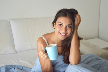 Portrait pretty girl drinking coffee or tea on bed in the morning in apartment with copy space