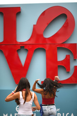 Girls prepare their hair before taking a photo in front of a love sign during the 6th annual Made in America Music Festival