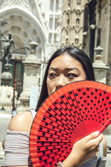 Chinese girl covering face with fan