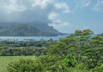 Hanalei bay on a cloudy day, with mountains and lush green landscape, on Kauai