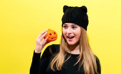 Girl wearing a cat knit hat holding a Halloween pumpkin