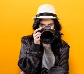 Young woman holding a camera on a yellow background