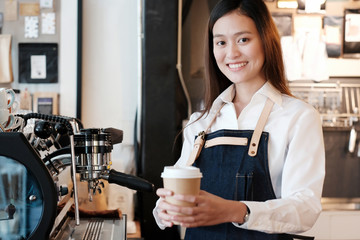 Young asian women Barista holding a take away coffee cup with smiling face at cafe counter background, small business owner, food and drink industry concept