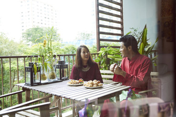 Young friends sharing cookies during Hari Raya