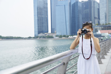 Young girl shooting with a camera at Raffles place, Singapore