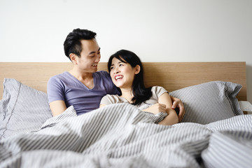 Husband and wife in bed cuddling