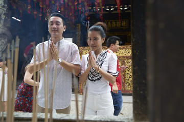 Lovely couple placing their joss sticks in a temple in Singapore