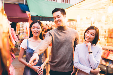 Group of three friends shopping in Chinatown, Singapore