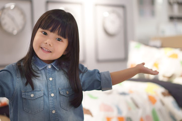 Asian children cute or kid girl wearing jeans and present or show my bedroom with modern clock on warm white because crazy or sales with space on soft focus and little noise at full picture size