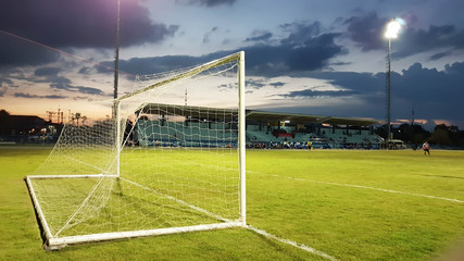 Football goal with the white mesh on a green lawn in the evening