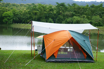 nature orange with green camping tent and gray fly sheet on meadow with lake or river and tree mountain for holiday relax on rainy season at ched khot