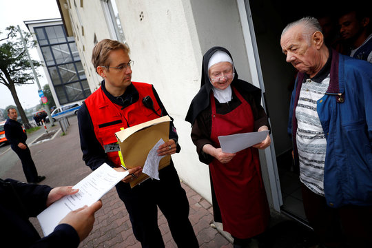 Sister Sigrid talks to firefighters and police officers as 60,000 people in Germany's financial capital are about to evacuate the city while experts defuse an unexploded British World War Two bomb in Frankfurt