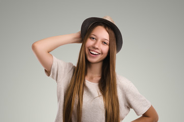 Positive casual woman posing. Emotional girl portrait. Young female with hat. The model is looking at the camera.